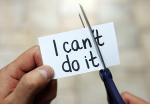 """Man using scissors to remove the word """"can't"""" to read """"I can do it"""" for self-belief, positive attitude and motivation."""
